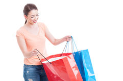 Smiling woman looking inside shopping bags as shopaholic concept Royalty Free Stock Photos