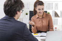 Smiling woman looking at laptop screen and talking to a colleagu Stock Image