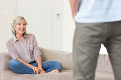 Smiling woman looking at man in living room Stock Images