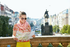 Smiling woman looking at map near National Museum in Prague. Catch the spirit of old Europe in Prague. Smiling young woman in sunglasses looking at the map near Stock Photos