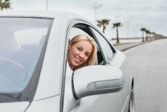 Smiling woman looking out from the car window Royalty Free Stock Photos