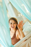 Smiling woman looking out from curtain Stock Images