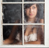 Smiling Woman Looking out Wet Window Royalty Free Stock Photos