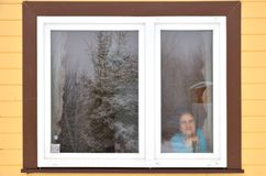 Smiling woman looking out window Stock Photos