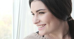 Smiling woman looking out through window. Beautiful smiling woman looking out through window stock footage