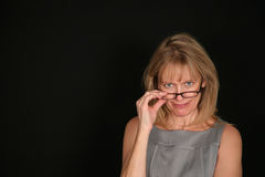 Smiling woman looking over glasses. Older woman looking over top of glasses Royalty Free Stock Photography