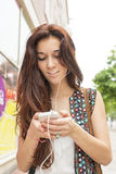 Smiling woman looking phone and listening music. Royalty Free Stock Photos