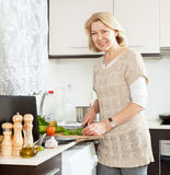 Smiling woman looking recipe  for cooking  in the internet Stock Image