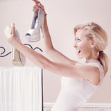 Smiling woman looking at shoes. Smiling beautiful blonde woman looking at fashionable high heels Stock Photo