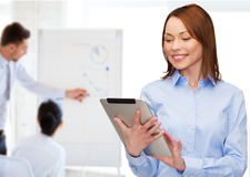 Smiling woman looking at tablet pc at office Stock Photography