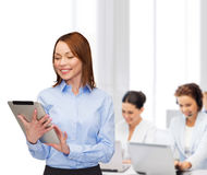 Smiling woman looking at tablet pc at office Royalty Free Stock Photography