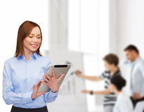 Smiling woman looking at tablet pc at office Stock Images