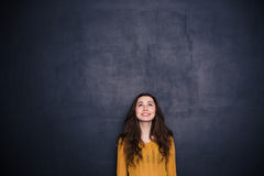 Smiling woman looking up at copyspace. Smiling young woman looking up at copyspace over black background Stock Images