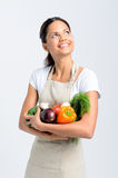 Smiling woman looking up with fresh produce Stock Image