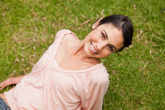 Smiling woman looking upwards while lying down Stock Images