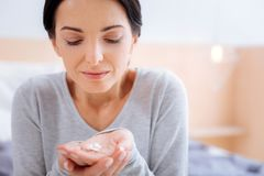 Smiling woman looking at the vitamins in her hand Royalty Free Stock Photos