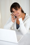 Smiling woman looking at you in front of laptop Royalty Free Stock Photography