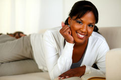 Smiling woman looking at you while lying on sofa Royalty Free Stock Image