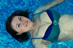 Smiling woman with loose hair swimming backstroke in a bi-color bikini swimsuit stock photography