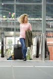 Smiling woman with luggage by escalator. Full body portrait of smiling woman with luggage by escalator Stock Images