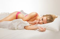 Smiling woman lying on bed Royalty Free Stock Image