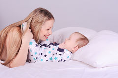 Smiling woman lying in bed with baby Royalty Free Stock Photography