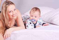 Smiling woman lying in bed with baby Stock Photos