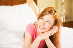 Smiling woman lying in bed dreaming looking up enjoying her morning. Portrait young beautiful smiling woman lying in bed dreaming looking up enjoying her morning Stock Photography