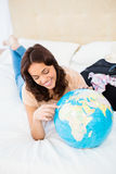 Smiling woman lying on bed while holding a globe Stock Photo