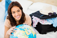 Smiling woman lying on bed while holding a globe. At home Royalty Free Stock Photo