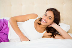 Smiling woman lying on the bed Stock Photo