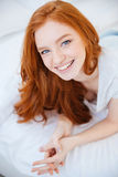 Smiling woman lying on the bed at home Stock Image