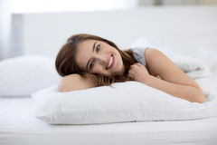 Smiling woman lying on the bed at home Royalty Free Stock Image