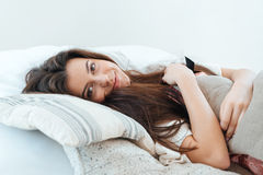 Smiling woman lying in bed and hugging pillow Royalty Free Stock Photo