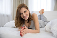 Smiling woman lying on the bed Stock Image