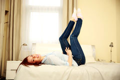 Smiling woman lying on the bed with raised legs Stock Images