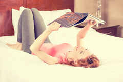 Smiling woman lying in bed while reading a magazine, travel guide stock photo