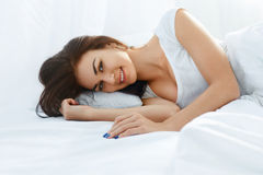 Smiling woman lying in bed Royalty Free Stock Photos