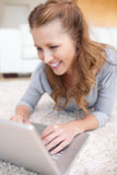Smiling woman lying on the carpet with her laptop Royalty Free Stock Photos