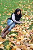 Smiling woman lying on a carpet of leaves Royalty Free Stock Image