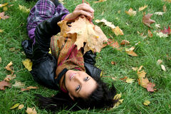 Smiling woman lying on a carpet of leaves Stock Photo