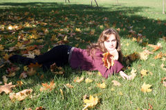 Smiling woman lying on a carpet of leaves Royalty Free Stock Photography