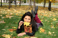Smiling woman lying on a carpet of leaves Royalty Free Stock Photos