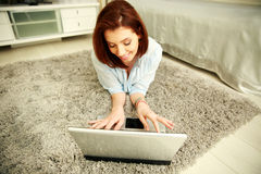 Smiling woman lying on the carpet and typing on the laptop Stock Photography