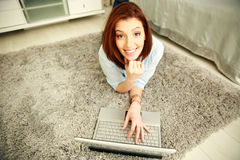 Smiling woman lying on the carpet and typing on the laptop Stock Image