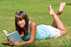 Smiling woman lying down on grass with book Stock Images