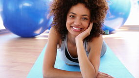 Smiling woman lying on exercise mat. At the gym stock video footage