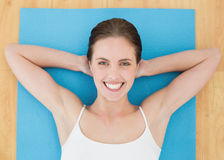 Smiling woman lying on exercise mat Stock Images