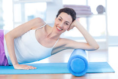 Smiling woman lying on exercise mat Stock Image