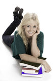 Smiling woman lying on floor with books. Happy young woman lying on studio floor with books stock photography